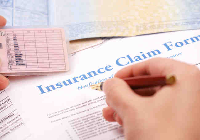 pen in hand filing insurance claim form